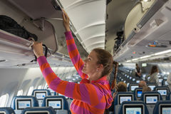 The young girl placed her hand luggage. Into the compartment on the plane Stock Photo