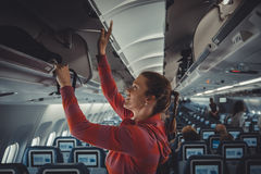 The young girl placed her hand luggage into the compartment. On the plane Stock Photos