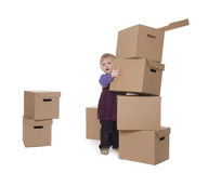 Young girl places from cardboards tower Stock Photos