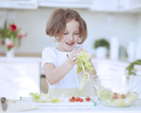 Young girl placing lettuce in salad bowl Royalty Free Stock Images