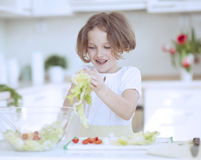 Young girl placing lettuce in salad bowl Royalty Free Stock Image