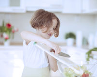 Young girl placing lettuce in salad bowl using a knife Stock Photography