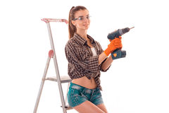 A young girl in a Plaid Shirt and glasses holding a drill near the stairs standing isolated on white background Stock Photo