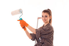 A young girl in a Plaid Shirt smiling and holding a roller for painting walls isolated on white background Royalty Free Stock Photos