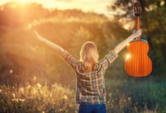 Young girl in a plaid shirt at sunset with an acoustic guitar Stock Image