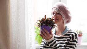 Young girl with plant in a pot stock footage