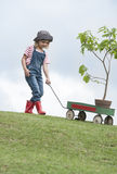 Young girl planting tree in park eco-aware. Young girl pulling cart up hill to plant tree in park eco-friendly Stock Image