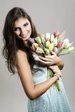 The young girl with plastic tulips Stock Photos
