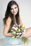 The young girl with plastic tulips Royalty Free Stock Image