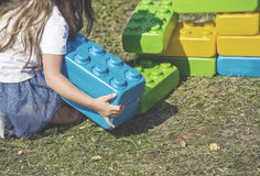 Young girl play with bricks in the garden, hdr effect Royalty Free Stock Photos