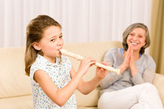 Young girl play flute with proud grandmother. Happy teacher clapping Stock Images