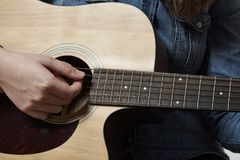 Young girl playing acoustic guitar with jeans shirt stock image