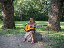 Young girl playing acoustic guitar outdoors in summer Stock Photography