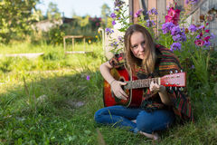 Young girl playing acoustic guitar sitting outdoors. Hippie. Stock Images