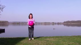 Young girl playing ball near a lake stock video