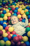 Young girl playing in a ball pool Royalty Free Stock Image