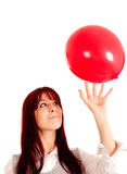 Young girl playing with a baloon. Beautiful young girl playing with a red baloon. Isolated against a white background Stock Photos