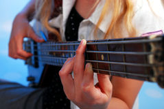 Young girl playing bass guitar on the stage. Close up on the fingers of young girl playing bass guitar on the stage Royalty Free Stock Images