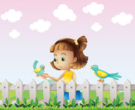 A young girl playing with the birds near the fence Stock Images