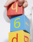 Young girl playing with blocks. Young girl playing with wooden toy blocks Royalty Free Stock Photography