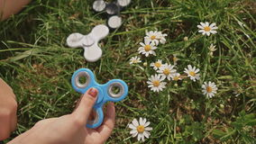 Young girl playing with a blue spinner on the lawn on a summer sunny day. stock footage