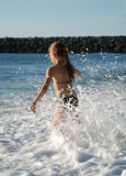 Young girl playing in the breaking waves. Stock Photos