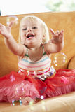 Young Girl Playing With Bubbles On Sofa Stock Photos