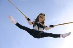 Young girl playing on bungee trampoline. Girl (5 years old) bouncing high in the air using a bungee trampoline Stock Photography