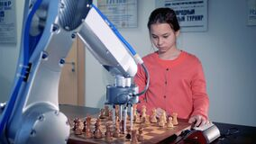 Young girl playing chess with a modern automated chess robot. Child genius concept. 4K.