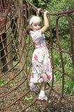 Young girl playing on climbing frame 02. Young girl playing on climbing frame with red net Royalty Free Stock Photo