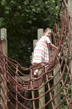 Young girl playing on climbing frame 03. Young girl playing on climbing frame with red net Stock Photo