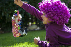 Young girl is playing with a clown Stock Photos