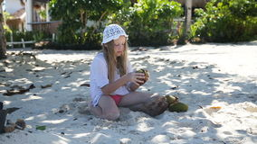 Young girl playing with coconut on the beach. stock footage