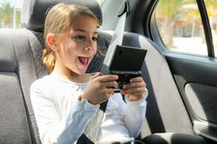 Young Girl Playing Console In Car Back Seat Royalty Free Stock Images
