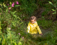 Young girl playing in deep puddle Stock Images