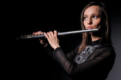 A young girl playing the flute Stock Photography