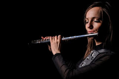 A young girl playing the flute Stock Photos