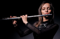 A young girl playing the flute Stock Image