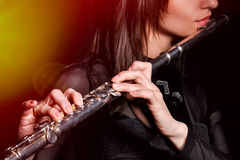A young girl playing the flute. Young elegant woman girl flutist flautist performer playing flute musical instrument on black Stock Photography