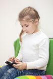 Young girl playing game on cellphone, sitting indoor Stock Photography
