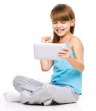 Young girl is playing game using tablet royalty free stock image