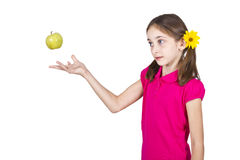 Young girl playing with green apple over white Stock Image