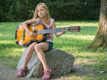 Young girl playing guitar. Young girl playing acoustic guitar outdoors in the park Stock Photos