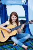 Young Girl Playing Guitar Against Tent Royalty Free Stock Image