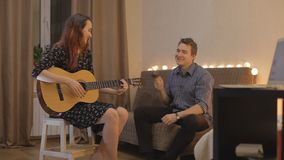 Young girl playing the guitar, the guy on the maracas stock footage