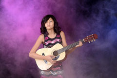 Young girl playing guitar on stage Royalty Free Stock Photos