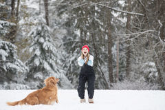 Young girl playing with her golden retriever dog in the winter s Royalty Free Stock Images