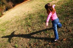 Young girl playing with her shadow. Young girl with her shadow stock photography