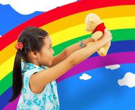 Young Girl Playing With Her Teddybear. In Her Playroom With Rainbow Wallpaper Royalty Free Stock Photo