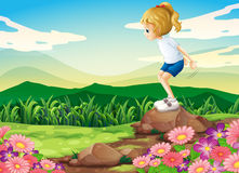 A young girl playing at the hilltop with rocks and a garden Royalty Free Stock Photo